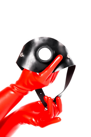 Red latex gloves holding a hollow gag on a strap.