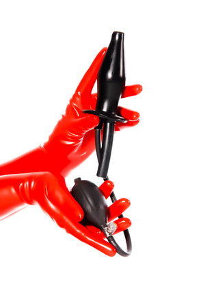Red latex gloves holding a large inflatable enema plug.