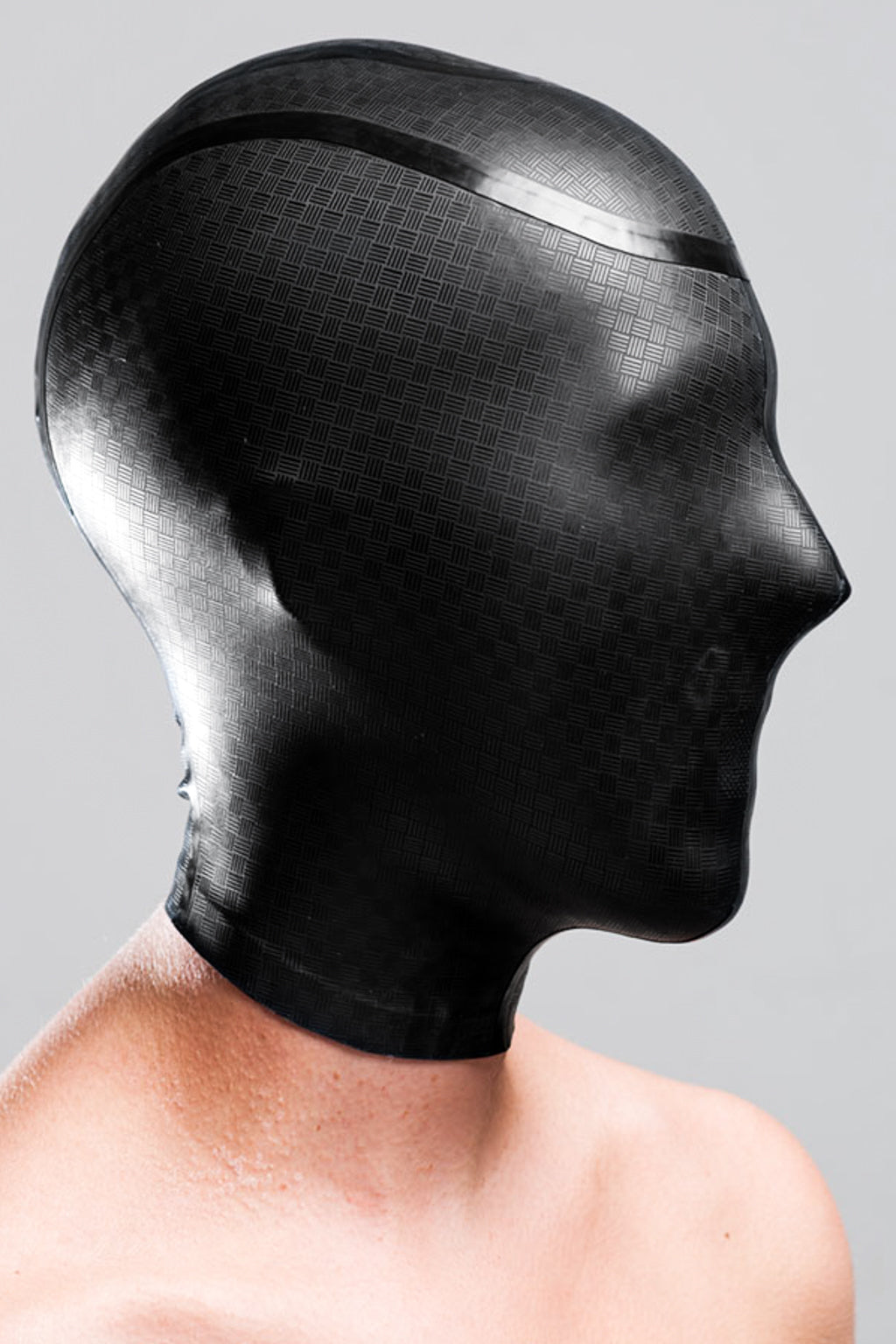 A person wearing a black laser etched micro breathe latex enclosure hood.