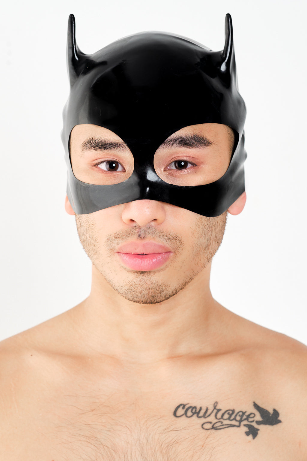 A man wearing a latex cat mask.