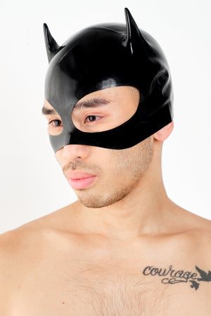 A man wearing a black latex cat mask.