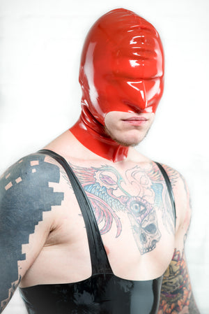A man wearing a latex leotard and a red latex hood with large mouth.