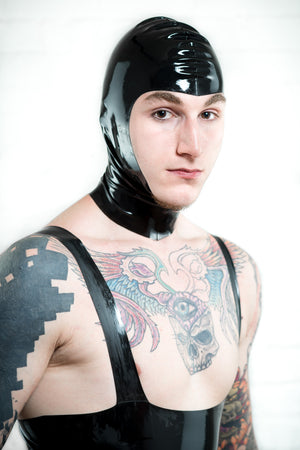 A man wearing a latex leotard and a black latex hood with open face.