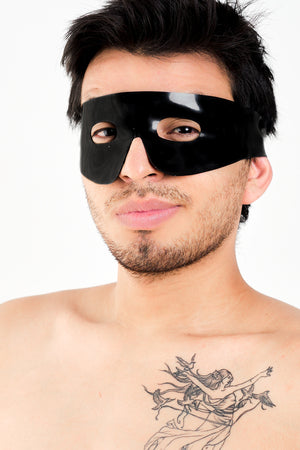 A man wearing a black latex Zorro mask.