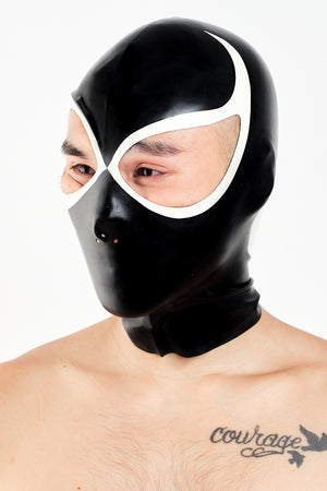 A man wearing a black and white lucha libre latex wrestling hood.