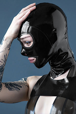 A woman wearing a rubberdoll cat eye latex hood, and a latex top.