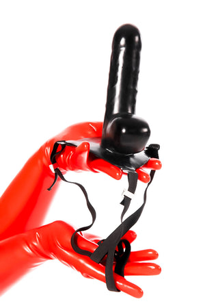 Red latex gloves holding a strap-on dildo.