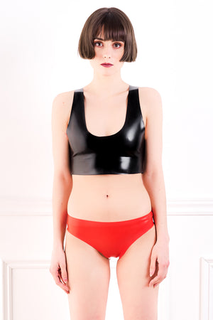 A woman wearing red latex bikini briefs with open crotch and a latex crop top.