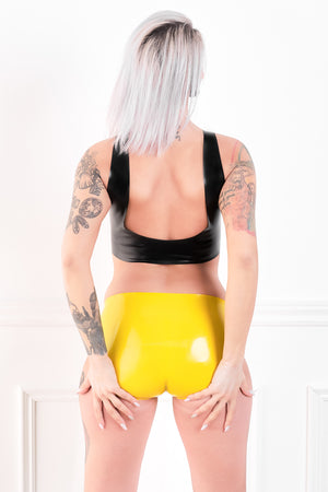 The back of a woman wearing yellow crotchless latex panty briefs. A rear view, showing her ass.