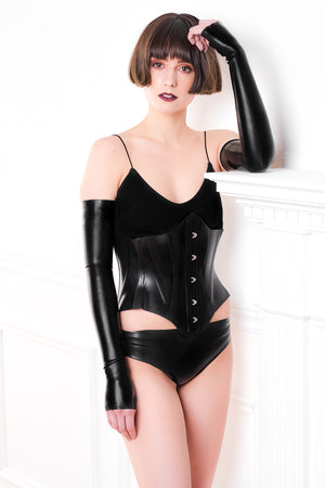 A woman leaning against a fireplace wearing fingerless latex shoulder gloves, a latex corset and latex panties.