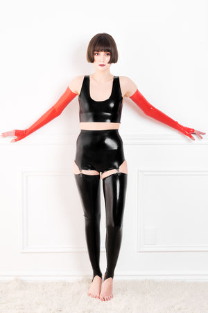 A woman wearing red fingerless latex shoulder gloves, a latex pantie girdle with latex stockings, and a latex top.