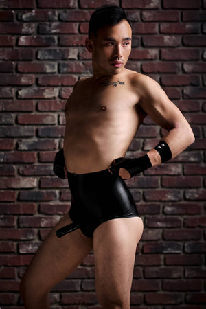A man wearing a pair of high waisted latex underwear with a penis sheath and a latex arm band.
