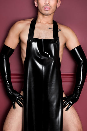 A man wearing a black latex apron and latex shoulder gloves.