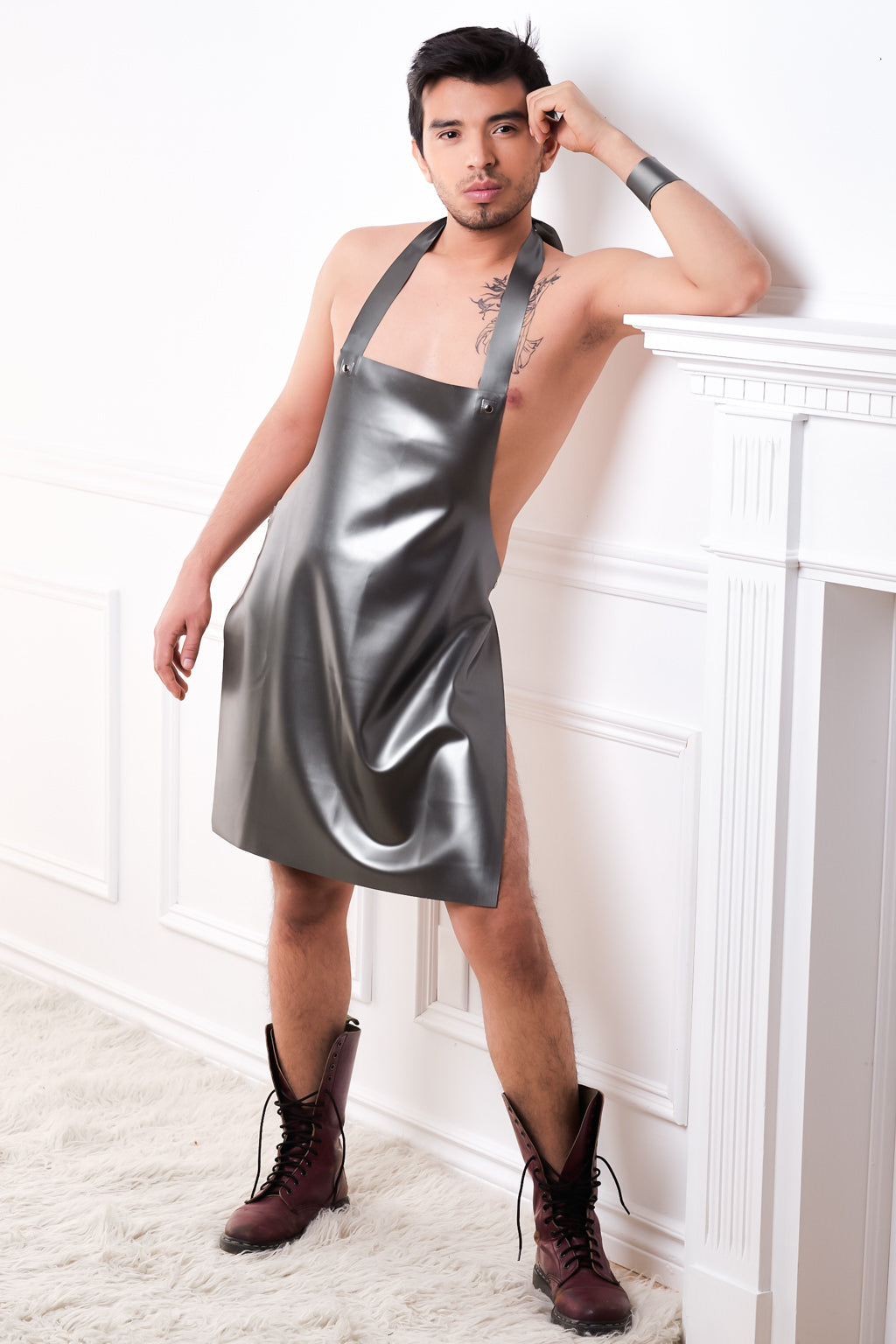 A man leaning against a fireplace wearing only a silver latex apron.