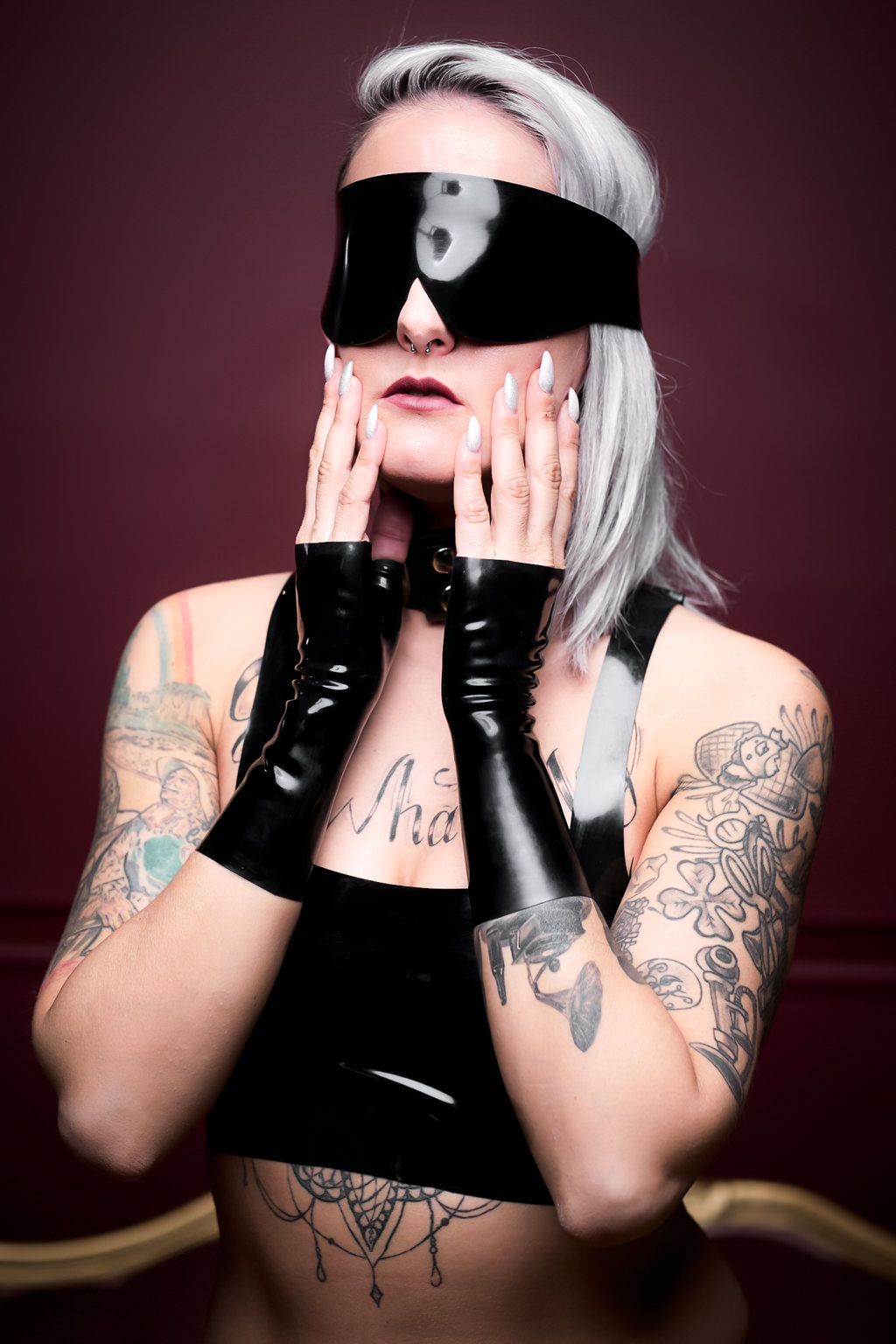 A woman wearing a latex blindfold and fingerless latex wrist gloves.