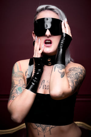 A woman wearing a latex blindfold, a latex choker and latex wrist gloves.