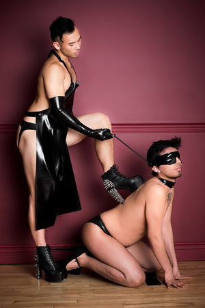 One man in a latex apron and latex shoulder gloves, the other wearing an inflatable latex blindfold.