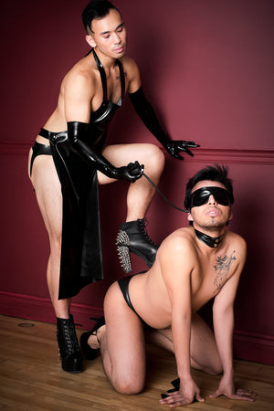 One man in heels wearing a latex apron and latex shoulder gloves, the other man wearing an inflatable latex blindfold.