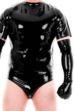 A man wearing a black latex t-shirt, latex briefs and latex bondage mittens.