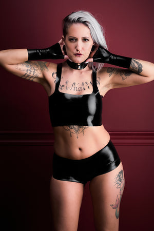 A woman wearing black latex boxer shorts with a latex camisole top and latex wrist gloves.