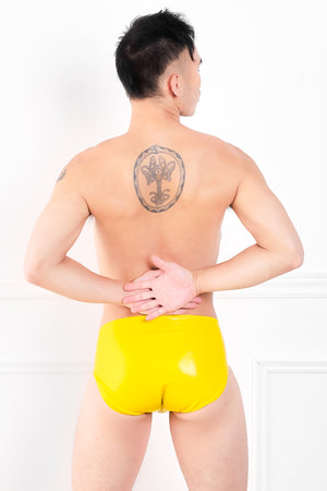 A man wearing yellow latex underwear with a penis sheath. A rear view, showing his ass.