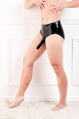 A man wearing latex briefs with a penis sheath and an anal sheath.