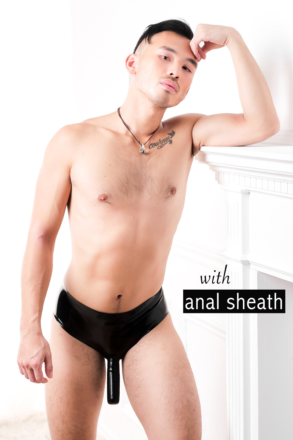 A man leaning against a fireplace wearing latex briefs with a penis sheath and an anal sheath.