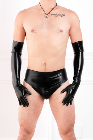 A man wearing black latex elbow gloves and latex briefs with an inflatable butt plug.