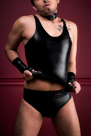 A man wearing black fingerless latex wrist gloves, a latex tank top and a pair of latex briefs with an inflatable butt plug.
