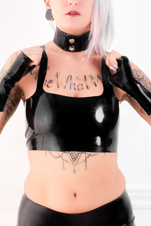 A woman in a latex camisole with a black latex choker.