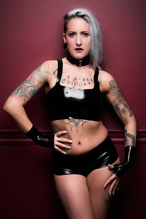 A woman wearing a latex outfit with a black latex camisole top.