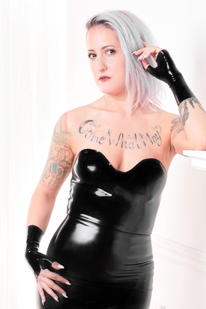 A woman wearing fingerless latex wrist gloves and a black latex cocktail dress.