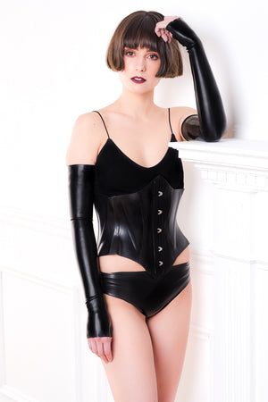 A woman wearing a latex corset, black fingerless latex shoulder gloves and latex panties.
