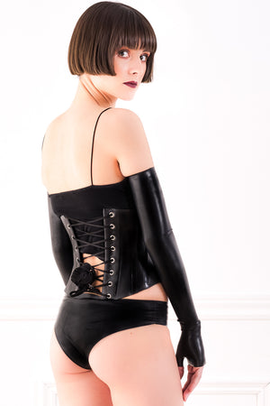 A woman wearing a black latex corset, latex panties and fingerless latex shoulder gloves. A rear view, showing the corset laces.
