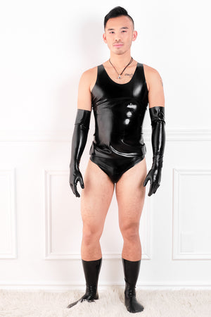 A man wearing a latex outfit consisting of latex elbow gloves, a latex shirt, latex briefs and latex socks.