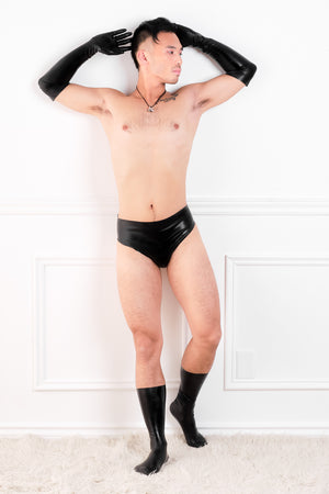 A man wearing a pair of black latex elbow gloves, latex underwear and latex socks.