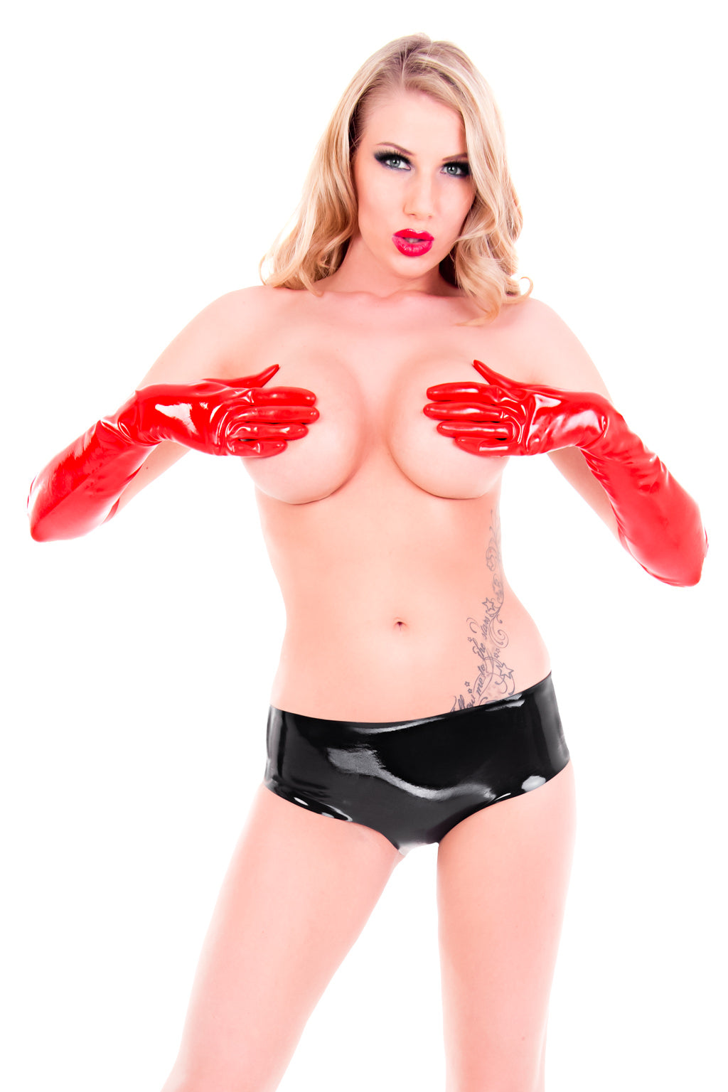 A woman only wearing a pair of latex hot pants and latex elbow gloves.