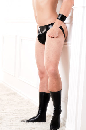 A man wearing a black latex jock strap, latex socks and a latex armband.