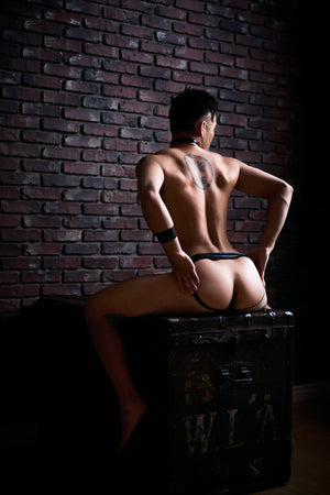 A man bent over on a trunk wearing a black latex jock strap. A rear view, showing his ass.