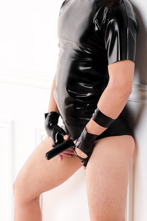 A man wearing a pair of black fingerless latex biker gloves, a latex t-shirt and latex briefs with a penis sheath and butt plug.