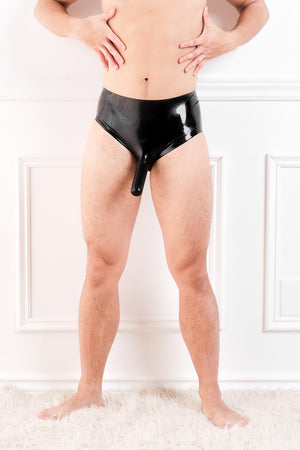 A man wearing black latex underwear with a penis sheath and butt plug.