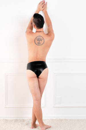 A man wearing a pair of black latex underwear with a penis sheath and butt plug. A rear view, showing his ass.