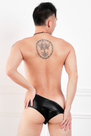 A man wearing a pair of black latex briefs with a penis sheath and butt plug. A rear view, showing his ass.