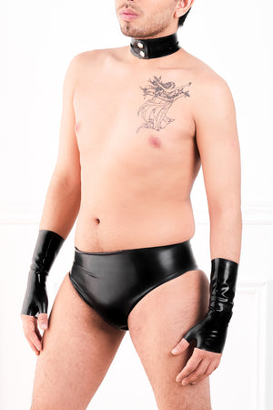 A man wearing fingerless latex wrist gloves, a latex choker and a pair of black latex briefs with a butt plug.