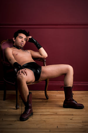 A man sitting in a chair wearing fingerless latex wrist gloves and black latex underwear with a butt plug.