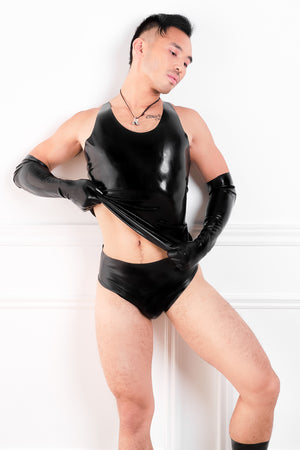 A man wearing black latex elbow gloves, a latex tank top and latex briefs with a butt plug.