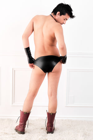 A man wearing fingerless latex wrist gloves and black latex briefs with a butt plug. A rear view, showing his ass.