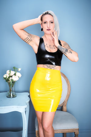 A woman standing beside flower wearing a black latex crop top and a yellow latex mini skirt.