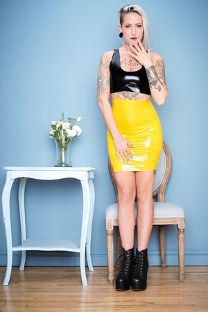 A woman standing beside some flowers wearing a black latex crop top and a yellow latex mini spanking skirt.