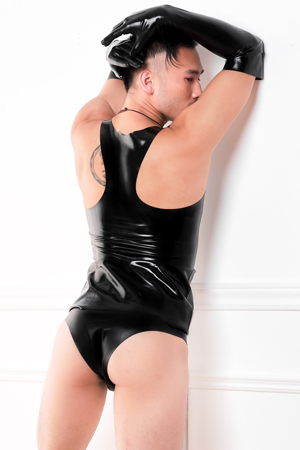 A man wearing a black latex muscle vest, latex elbow gloves and latex underwear. A rear view showing the back.